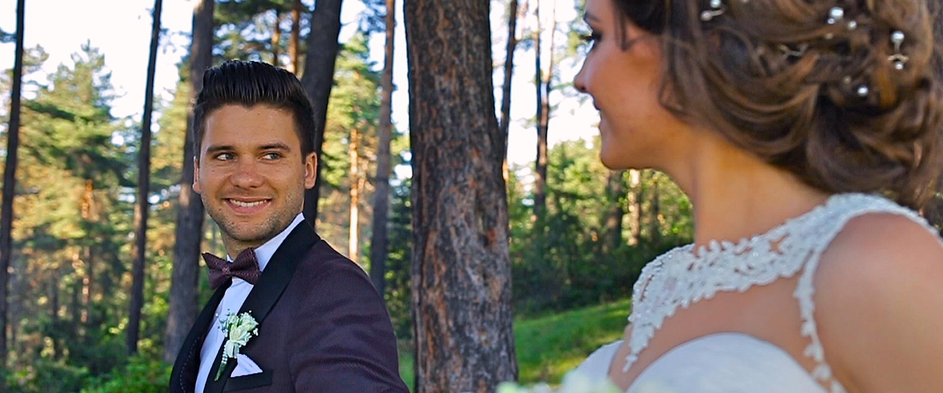 Groom looking at his bride while walking in the forest - Carpathian Mountains