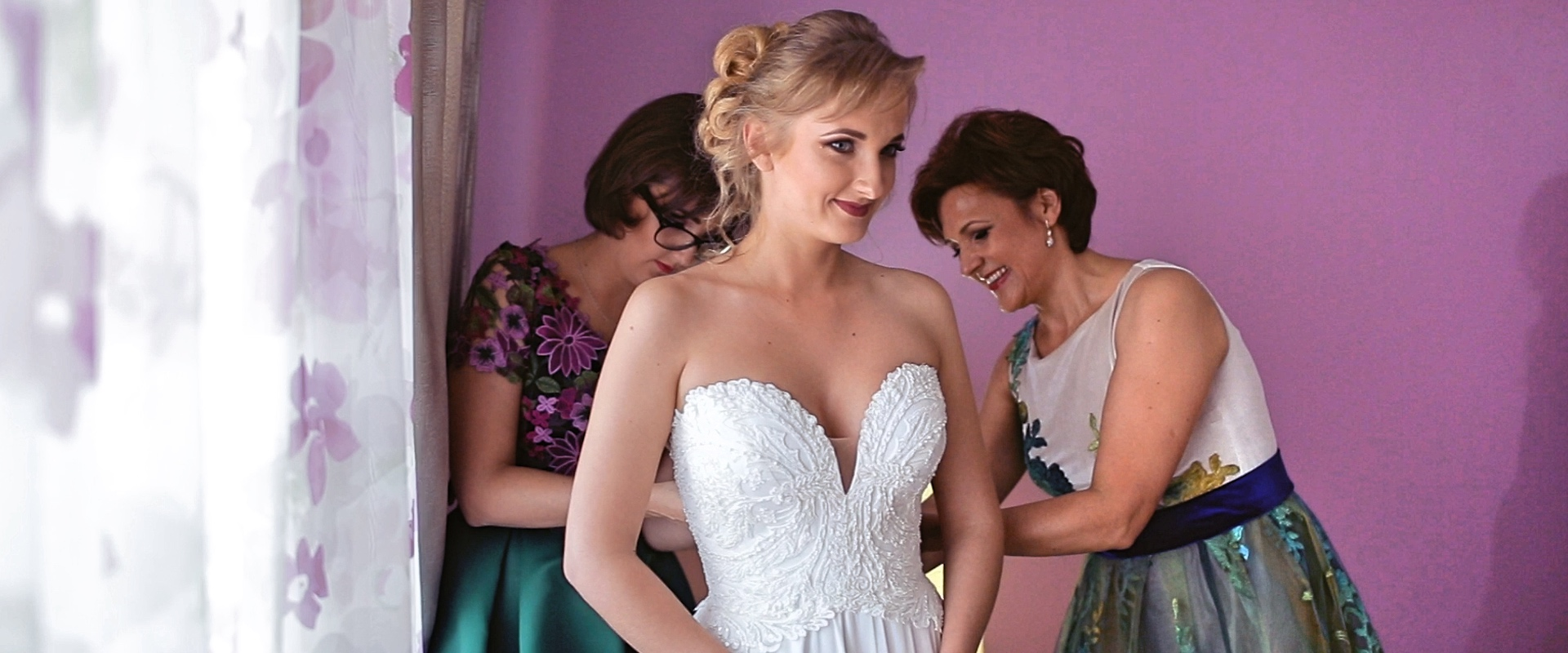 Bride getting ready, being helped by her mother